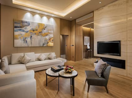 Presidential Suite Living Room with Corner Sofa, Coffee Table, Chair and Wall Mounted HDTV