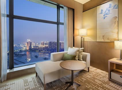 Chaise Lounge by Large Window with Bay View in the Evening