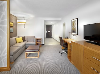 Accessible Guest Room Lounge Area with Sofa, Television and Work Desk