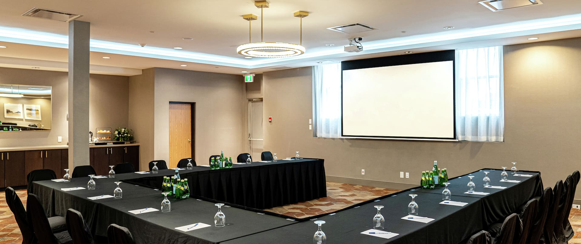 a u-shaped meeting table and a presentation screen in a room