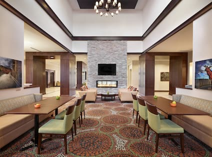 Booth Seating With Green Chairs in Breakfast Dining Area and View of Lounge Seating by Fireplace With TV