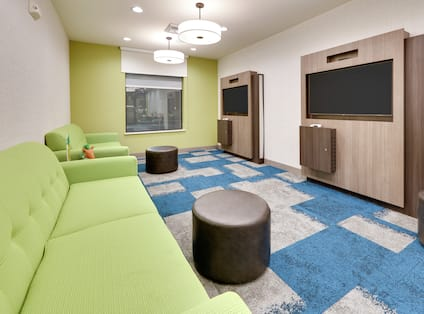 Room with green couches and 2 TVs