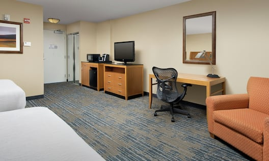 Desk Armchair Microfridge Coffeemaker Mirror and HDTV in Guest Room
