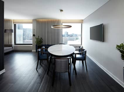 Guest Suite Dining Area with Chairs, Table and Wall Mounted TV
