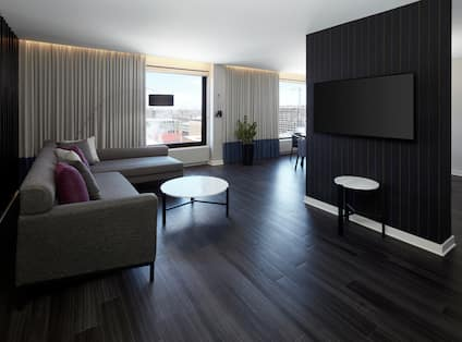 Guest Suite Living Area with Sofa, Coffee Table and Wall Mounted TV