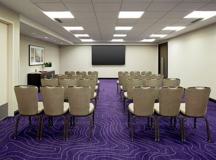 Meeting Room with Rows of Chairs and Wall Mounted TV