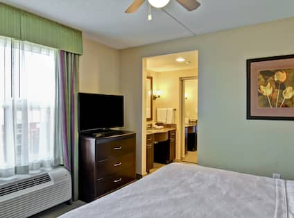 Wall Art, Ceiling Fan Above King Bed, TV by Window, and Door Opening to Bathroom