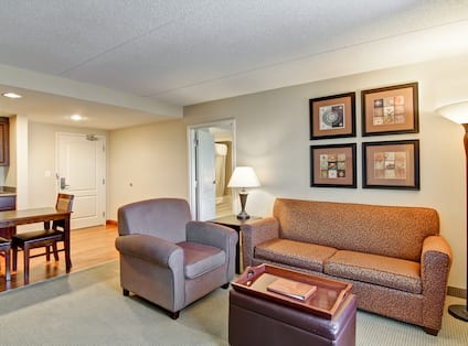 Studio Living Area With Wall Art, Lamps, Soft Seating, Dining Table, Kitchen, Entry, and Open Doorway to Bedroom