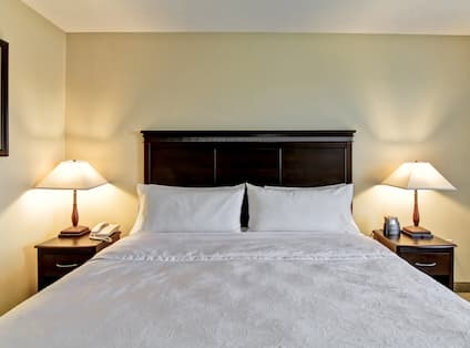 Wall Art, Neatly Made King Bed, and Illuminated Lamps on Bedside Tables