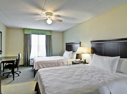 Ceiling Fan Above Two Queen Beds, Illuminated Lamp on Bedside Table, TV, Work Desk and Window With a View in Accessible Guest Room