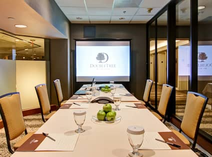 Small Conference Meeting Room with Seats, Projector Screen and Table with Notepads
