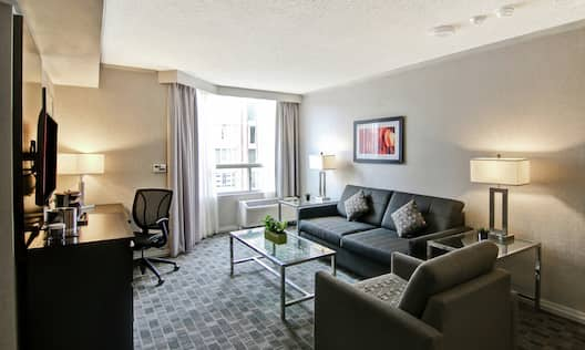 2 Room Deluxe Suite Living Area with Sofa Table Chair Desk and HDTV