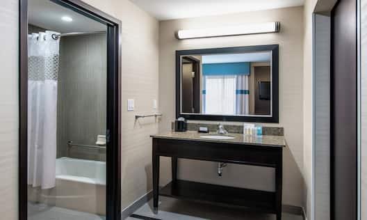 King Studio Suite Bathroom with Mirror, Vanity, Bathtub, and Shower