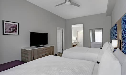 guest room with two beds and television