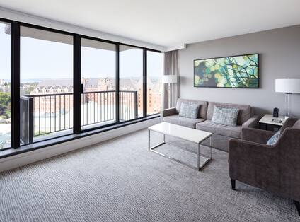 Left-Facing Sofa, Chair, Coffee Table, Wall Art, Two Floor Lamps by Large Windows in Family View Suite