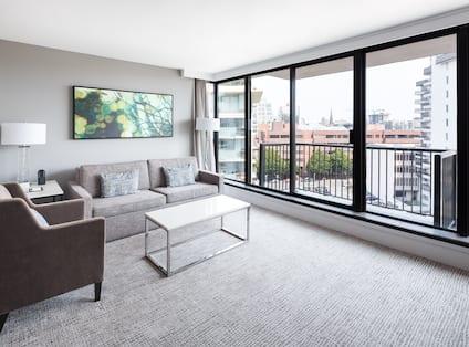 Sofa and Soft Chair with Coffee Table, Mounted Art, and Two Floor Lamps  by Large Windows With Balcony in Family Suite Living Area