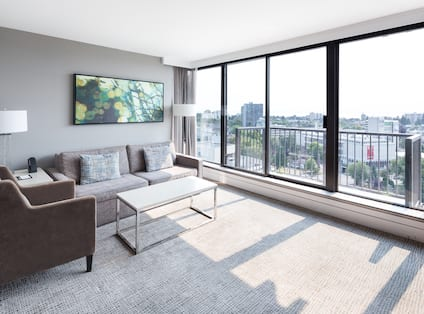 Living Room Suite Area With Sofa, Chair, Table, Floor Lamps and Floor to Ceiling Balcony Windows that Overlook the City