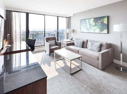 Sofa, Mounted Art, Soft Chair, Floor Lamps, Coffee Table, and a Work Desk With Task Chair Near a Large Window With a Balcony in Suite Living Area