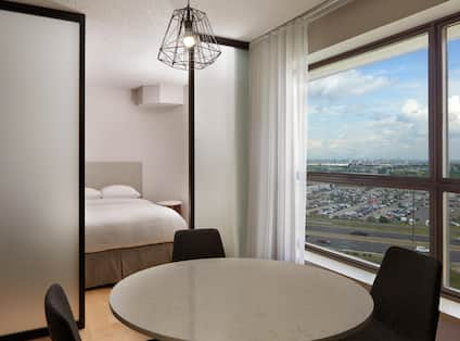 Round Table with Chairs and a Bed in Guest Room with Large Windows