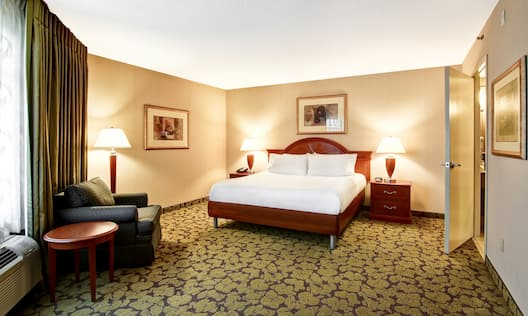 Wall Art, King Bed, Illuminated LAmps, Armchair, and Open Doorway to Separate Living Area. in Suite