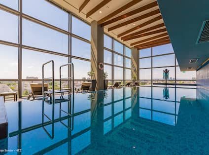 Indoor swimming pool with floor to ceiling windows and views of the city and outdoors