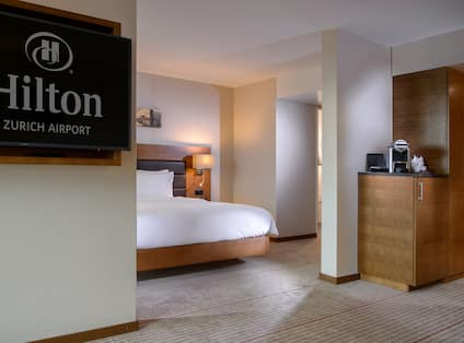 Angle View of Queen Junior Suite with Hilton Logo