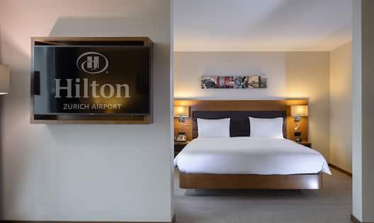 Queen Junior Suite Bedroom with Hilton Logo